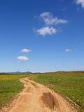 Road with mud. Landscape with a road with mud and mountains in the distance stock image