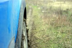 Road with mud, side view of car. Focus on the tire stock photos