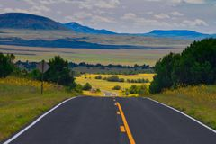 New Mexico Fantasy Highway. Road near Capulin, New Mexico with a fantasy like appearance. Flowers, valley, mountains royalty free stock photo