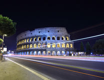 Road near old stone walls of Coliseum. At summer night in Rome, Italy Stock Photo