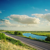 Road near river under clouds in blue sky Stock Photography