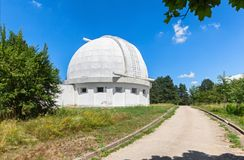 Road next to the Observatory building with a retractable dome for the coronograph. The dome of the telescope during the day Royalty Free Stock Photos