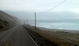 Road next to the ocean on a foggy day stock image
