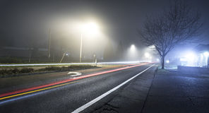 Road at night with fog and long exposure of car Royalty Free Stock Image