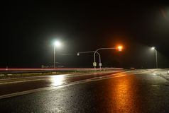 Road lights illuminate the empty track. Road at night in the fog. Road lights illuminate the empty track royalty free stock image
