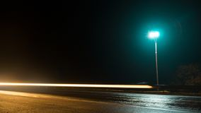 Road lights illuminate the empty track. Road at night in the fog. Road lights illuminate the empty track stock images