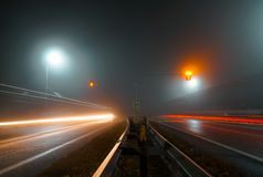 Road lights illuminate the empty track. Road at night in the fog. Road lights illuminate the empty track stock image