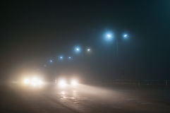 Road. Night. Fog. Streetlights. Headlights Stock Photos