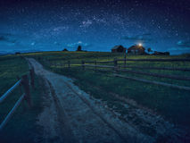 Road through the night village. Majestic starry sky above the Carpathian valley Royalty Free Stock Photography