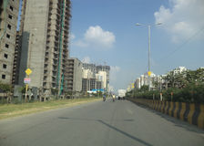 Road in NOIDA. Uttar Pradesh, India. Apartments getting constructed on the left side of the road Royalty Free Stock Photography