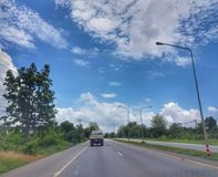 On The road from Nongkhai to Khonkaen, Thailand. Beautiful blue sky and green scenery along the side of the road from Nongkhai, Udon and Khonkaen, Thailand Royalty Free Stock Image