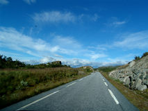 Road. Norwegian road with clouds in the background royalty free stock image