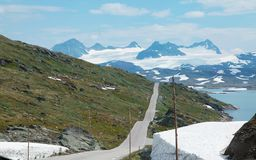 Road in norwegian fjords. One empty road in norwegian fjords and snowy mountains Royalty Free Stock Photos