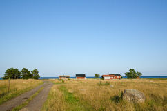 Road and old cabins. Fishermen´s old cabins by the coast of Baltic sea Royalty Free Stock Photos