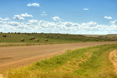 Road through open prairie. A view of a wide, open roadway passing through open prairie with baled hay in Canada stock images