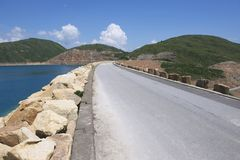 Road over the dam of the High Island Reservoir at the Hong Kong Global Geopark, Hong Kong, China. Stock Images