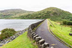 Road over dam of Llyn Cwmystradllyn reservoir. Royalty Free Stock Photos