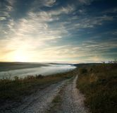 Road over village and hills in morning mist on background of sky Stock Photo