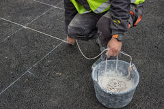 Road paint worker with chalk line. String covered in chalk dust. ping a chalk line to mark a line down and preparing for marking new road lines Stock Image