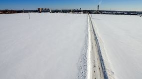 The road passes through a smooth line. Along the snow-covered field Stock Photos
