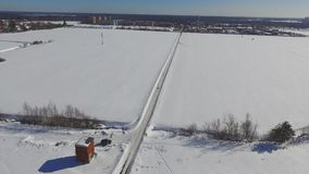 Flight over the winter road through the field stock footage