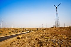 Road passing through a desert with wind turbines in distance, Ja Royalty Free Stock Photos