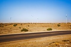Road passing through a desert with wind turbines in distance, Ja Royalty Free Stock Image