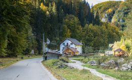 The road passing through the farm at the foot of the Carpathian Mountains near the town  of Bran in Romania Royalty Free Stock Images