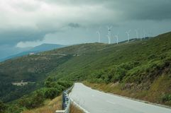 Road passing through hilly landscape with several wind turbines. Countryside road passing through hilly landscape with several wind turbines, in a cloudy day at royalty free stock photography