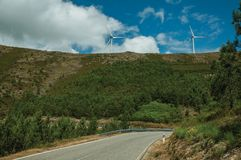 Road passing through hilly landscape with wind turbines. Countryside road passing through hilly landscape with several wind turbines, in a sunny day at Serra da stock images
