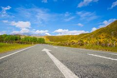 Road Passing Through Landscape Against Blue Sky Stock Photography