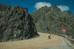 Road passing through rocky landscape with cyclist. Curve on roadway passing through rocky landscape with cyclist pedaling on slope, at the highlands of Serra da stock photography