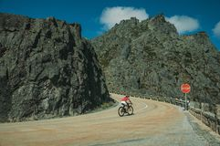 Road passing through rocky landscape with cyclist. Curve on roadway passing through rocky landscape with cyclist pedaling on slope, at the highlands of Serra da royalty free stock images
