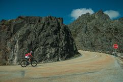 Road passing through rocky landscape with cyclist. Serra da Estrela, Portugal - July 14, 2018. Curve on roadway passing through rocky landscape with cyclist, at royalty free stock photography