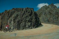 Road passing through rocky landscape with cyclist. Serra da Estrela, Portugal - July 14, 2018. Curve on roadway passing through rocky landscape with cyclist, at stock photo