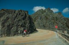 Road passing through rocky landscape with cyclist. Serra da Estrela, Portugal - July 14, 2018. Curve on roadway passing through rocky landscape with cyclist, at stock image