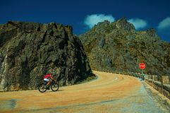 Road passing through rocky landscape with cyclist. Serra da Estrela, Portugal - July 14, 2018. Curve on roadway passing through rocky landscape with cyclist, at stock images