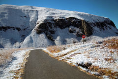 Road Passing Through Snow Covered Mountains. A road winds away into the distance of snow covered mountains. To the right, a Do Not Enter sign is visible royalty free stock photography