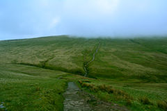 Road/path on a green hill covered with low cloud,  Pen y Fan peak, Brecon Beacons , Wales, UK. Brecon Beacons National is a Park in Monmouthshire, south east Royalty Free Stock Photos