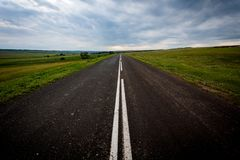 Asphalt road with fresh markings rests against the clouds. Road, path, marking, clouds, asphalt road with fresh markings rests against the clouds. travel by road Royalty Free Stock Image
