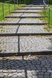 Road Paved with Brick-Stones with a Shadowy Leading Line Stock Photos
