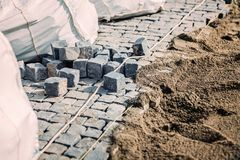 Road pavement. Stone granite blocks install details. Cobblestone rocks placement on sidewalk Stock Photo