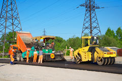 Road paving with truck, rolling machinery and workers Stock Photography