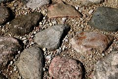 The road, a pedestrian path made of stones of different shapes. Background Stock Photos