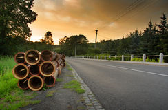 Road and Pipes. Road in the country, orange sunset sky and stack of pipes Stock Image