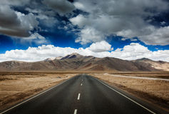 Road on plains in Himalayas with mountains Stock Photo