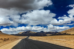 Road on plains in Himalayas with mountains Royalty Free Stock Photography