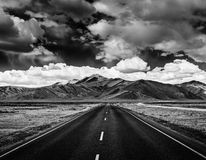 Road on plains in Himalayas with mountains Stock Image