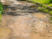 Road with potholes. Broken road with potholes and puddles Royalty Free Stock Photo