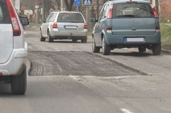 Road with potholes. A road with potholes and cars driving by Stock Photos